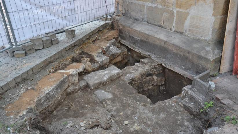 """""""Dort muss ein bisher unbekanntes Vorgängergebäude gestanden haben."""" Nur wenige Zentimeter über dem Fundament verläuft heute das Pflaster der Bamberger Straße, die direkt am eingezäunten Grundstück entlangführt. Immer weiter graben sich die Wissenschaftler in den Boden vor, bis sie tatsächlich auf ihn stoßen: einen Zugang in den Raum voller Knochen."""