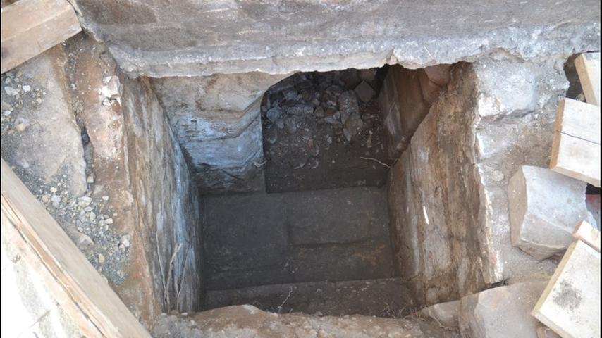Zum ersten Mal seit Jahrhunderten erhellt das Tageslicht das Gewölbe, nachdem die Archäologen Erde und Steinreste entfernen. Als wären die Knochen nicht schon spektakulär genug, entdecken die Forscher in dem Geröll einen größeren Brocken Stein, einen Marter.