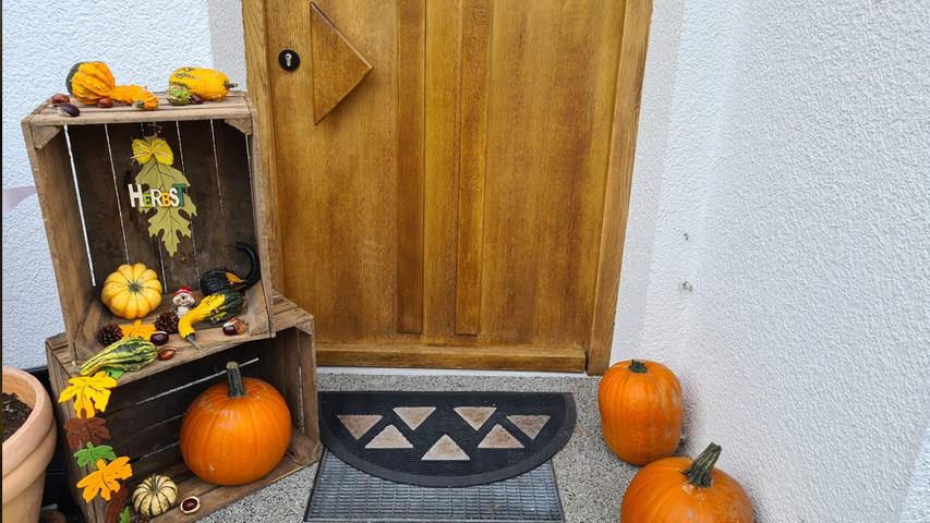 Kürbisse als Dekoration: Zierkürbisse sehen vor der Haustüre wirklich schön aus. Zusammen mit Blättern und Kisten kommt Herbststimmung auf.