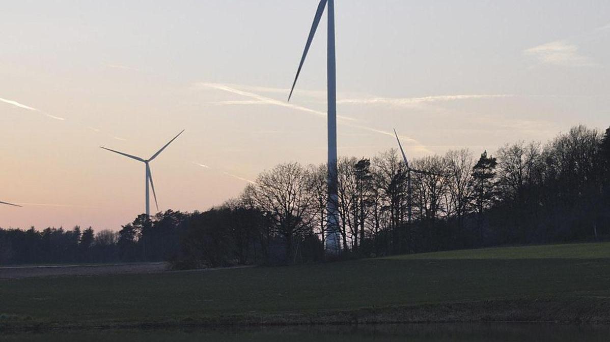 """Bei Lonnerstadt spiegeln sich Windräder in einem Weiher. """"Es ist die Zukunftsbranche schlechthin"""", meint Projektentwickler Stefan Paulus."""