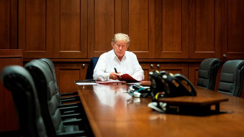 Kurz nachdem er wegen seiner Infektion mit dem Corona-Virus in einem Militärkrankenhaus behandelt wurde, präsentiert sich Trump mit Akten im Konferenzraum.