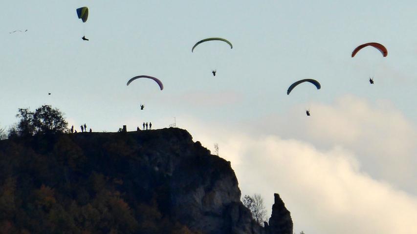 """Paraglider am Walberla – ein Foto von NN-Leser Norbert Haselbauer vom letzten Samstag mit jeder Menge Paraglidern am Walberla. Bis zu zehn Paraglider gleichzeitig flogen zeitweise über das Walberlaplateau. Viele Zuschauer waren da natürlich garantiert. Übrigens, der markante Felsen rechts unten ist die so genannte """"Steinerne Frau""""."""