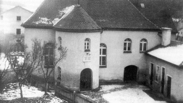 Die einstige Treuchtlinger Synagoge samt jüdischer Schule in der Uhlengasse vor ihrer Zerstörung durch die Nationalsozialisten in der Pogromnacht vom 9. November 1938. Heute befinden sich dort ein Wohnhaus und ein Garten. Die Treuchtlinger Bürger beteiligten sich äußerst aktiv an den Plünderungen und Gewalttaten der Nazis. Jüdische Mitbürger wurden gedemütigt, misshandelt und beraubt, mindestens einer in den Selbstmord getrieben. Bald darauf meldete sich die Stadt als eine der ersten in der Region