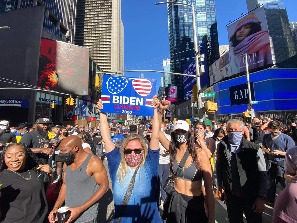 People celebrate at Times Square in New York after Joe Biden was declared winner of the 2020 presidential election on November 7, 2020 (Photo by Kena Betancur / AFP)