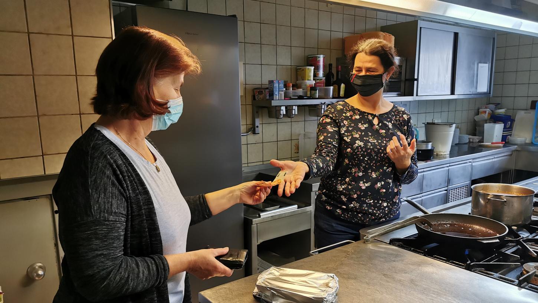 Eine Kundin übergibt Wirtin Sandra Hetzner aus Unterwurmbach das Geld für ihr bestelltes Essen.