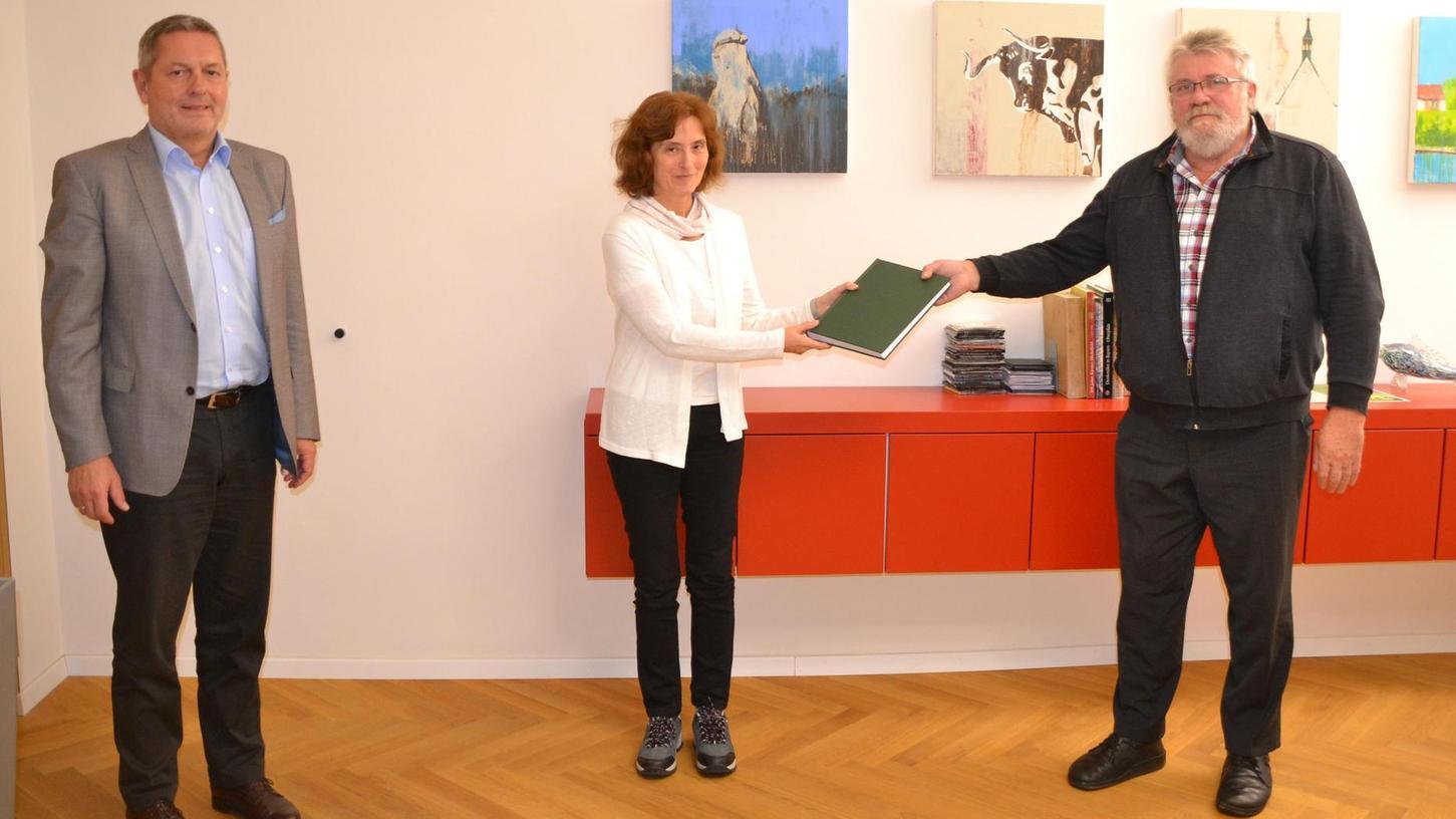J. Michael Suttner (rechts) aus Neuhaus hat einen weiteren Band der Köstler-Chronik übersetzt und an Doris Bundscherer und Bürgermeister Neuß überreicht.