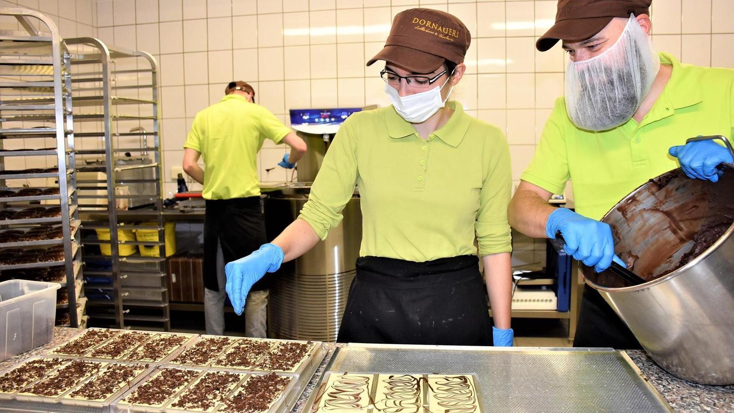 Ohne Schokolade geht hier nichts: Firmenchef Thomas Dornauer (rechts) und seine Auszubildende Rebecca Kohler beim Verzieren von Leckereien, nach denen sich selbst Kunden aus Übersee die Finger lecken.