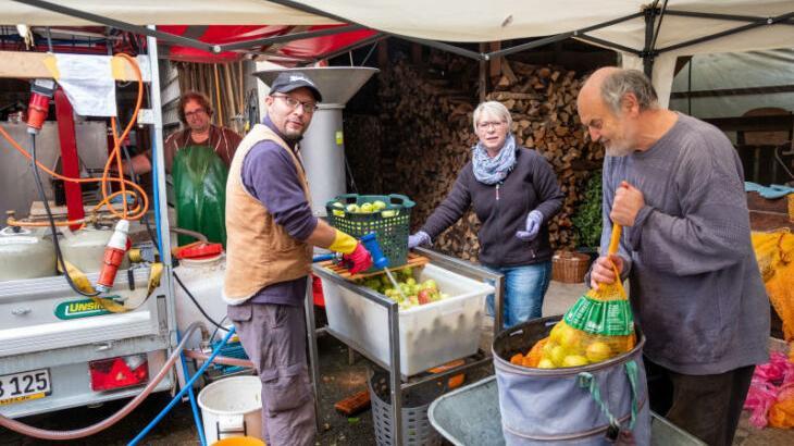 Alle packten beim Pressen der Äpfel an der mobilen Maschine an, auch Pfarrer Gerhard Metzger (rechts).
