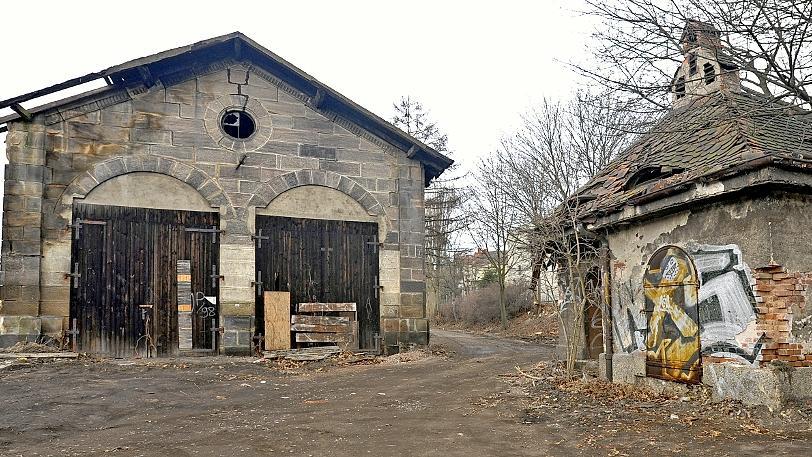 Ein Bild des Jammers: Der historische Lokschuppen und die kleine Schmiede rechts daneben. Durch das marode Dach dringt Nässe ins Mauerwerk — deutlich sichtbar an der Verfärbung der Sandsteine.
