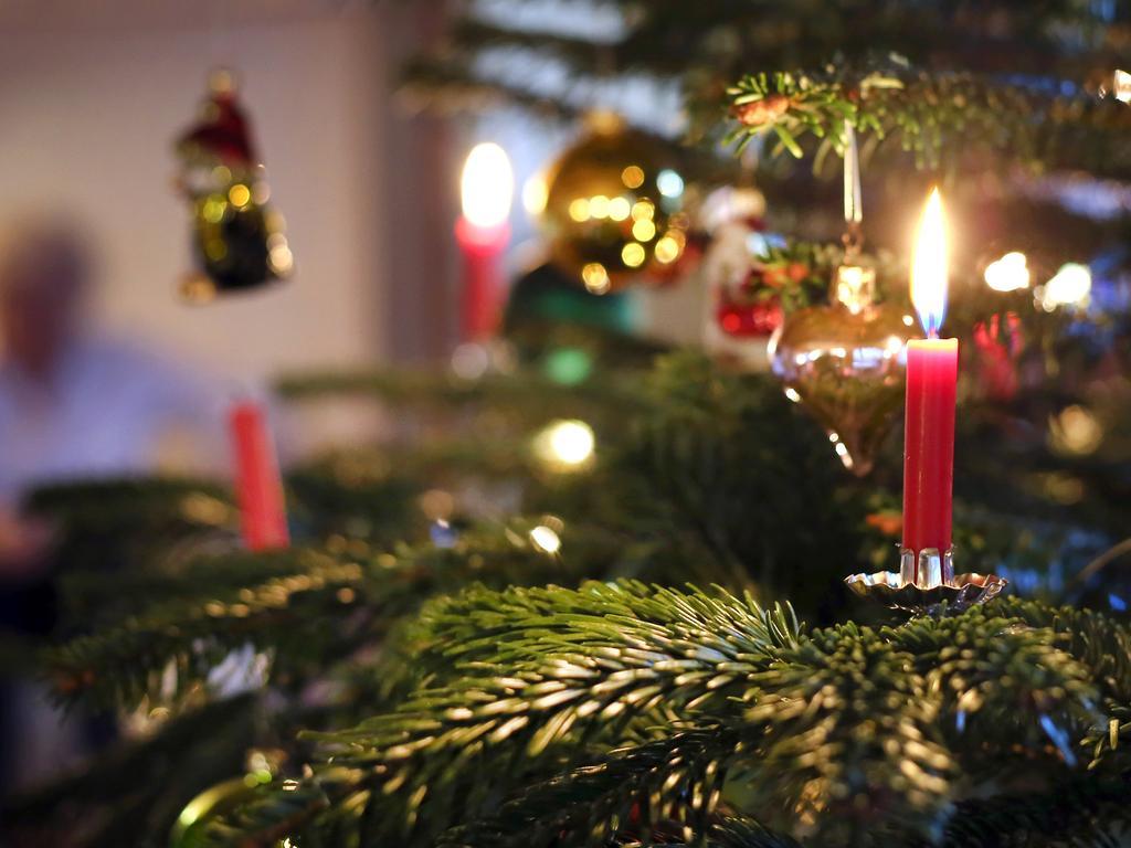 ARCHIV - 25.12.2019, Bayern, Kaufbeuren: Kerzen brennen an einem festlich geschmückten Weihnachtsbaum. Bundeskanzlerin Merkel und die Länderchefs wollen sich zu einer Video-Konferenz zusammenschalten und anschließend über die Ergebnisse informieren. (zu dpa