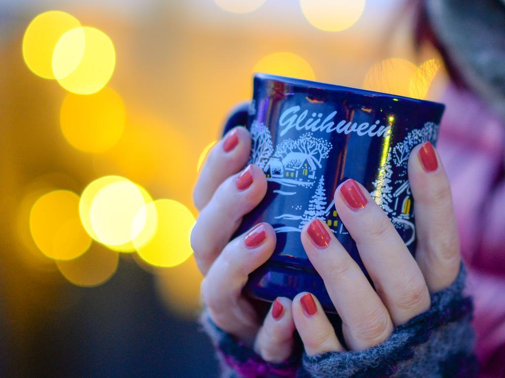 ARCHIV - 18.12.2018, Berlin: Eine Frau hält eine Tasse mit Glühwein in den Händen. Die meisten Weihnachtsmärkte in Niedersachsen sind in der Corona-Pandemie abgesagt - vielen Städten gehen damit Zehntausende Euro verloren. (zu dpa