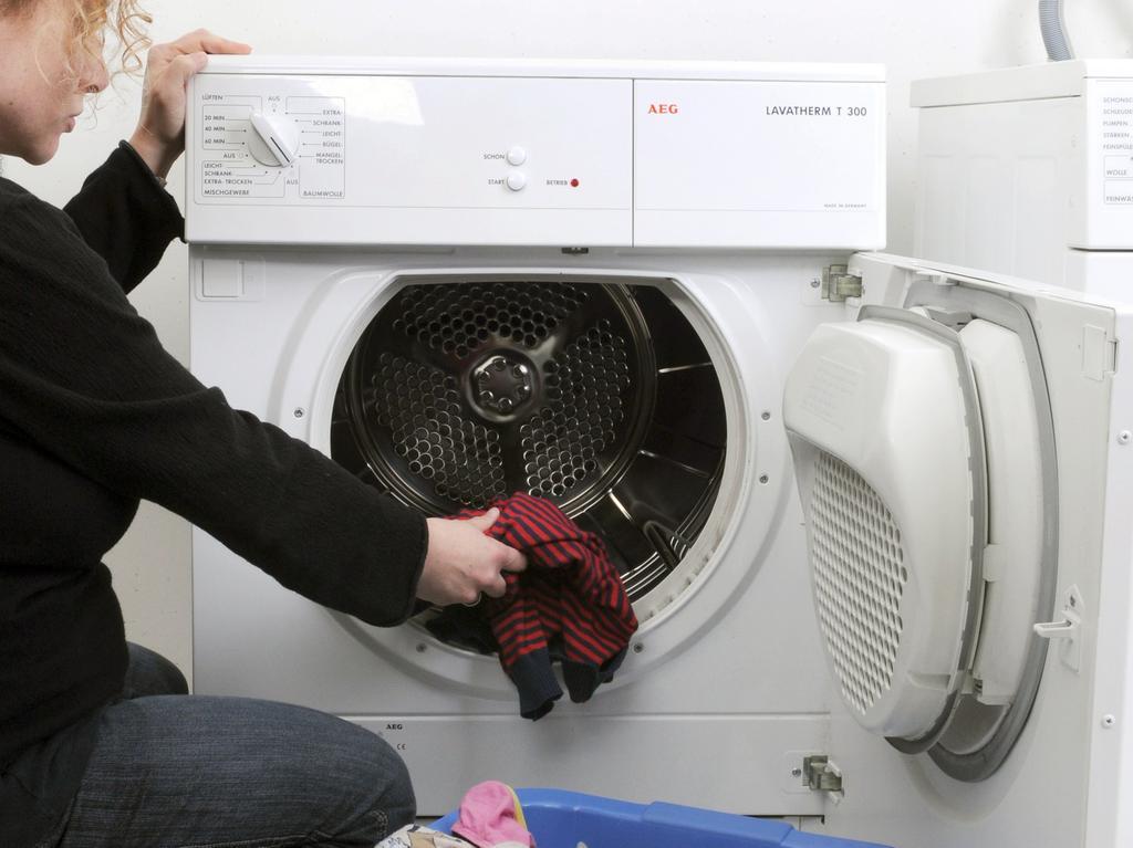 ARCHIV - Eine Hausfrau befüllt einen Wäschetrockner mit Kleidung, aufgenommen  am 24.03.2009 in Straubing (Niederbayern). Pünktlich zum Vatertag wird ein  beliebtes Vorurteil bestätigt: Frauen putzen doppelt so viel wie Männer. Egal,  ob Abwaschen, Staubsaugen oder Wäschewaschen - damit verbringen nach dem  Ergebnis einer repräsentativen Umfrage Männer durchschnittlich nur 34 Minuten  am Tag. Frauen sind dagegen mehr als eine Stunde (62 Minuten) im Haushalt  beschäftigt. Foto: Armin Weigel dpa/lby (zu dpa 0011 vom 11.05.2010) +++(c) dpa  - Bildfunk+++