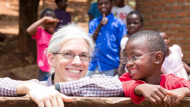 Der Erfinder der Ein-Dollar-Brille Martin Aufmuth mit einem Jungen in Malawi – beide wirken sehr glücklich mit ihrer Brille.