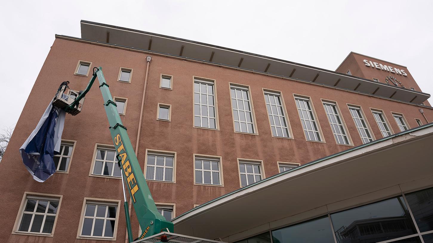 Neues Leben in einem der markantesten Gebäude in der Region. Am Himbeerpalast wird ein FAU-Transparent angebracht, um den Übergang von Siemens auf die Friedrich-Alexander-Universität zu signalisieren.