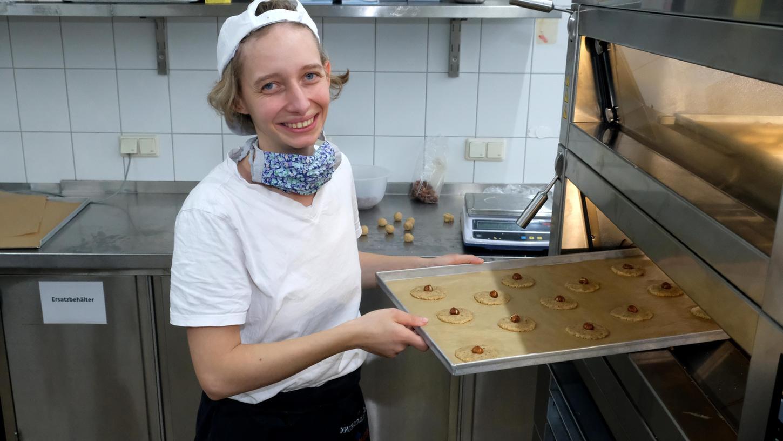 Fürs Foto mal die Maske runter, damit man ihr Lachen sieht: Hannah Feneberg baut in der Gastro-Firma der Lebenshilfe die Konditorei auf.