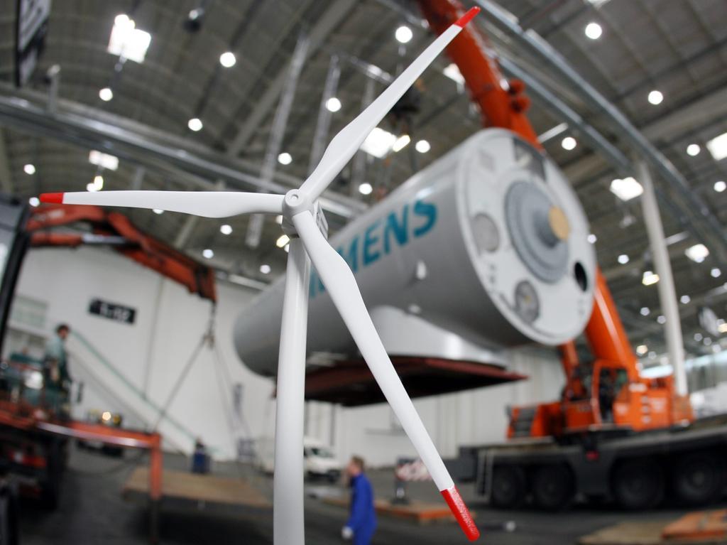 ARCHIV- Das Modell einer Windkraftanlage ist am 09.05.2006 vor einem 87 Tonnen schweren Maschinenhaus einer Offshore Windkraftanlage der Siemens Wind Power GmbH auf dem Hamburger Messegelände zu sehen. Die 2,3 Megawatt-Anlage wurde unter anderem im süddänischen Offshore-Windpark Nystedt in der Ostsee errichtet. Nach unbestätigten Medienberichten traf sich der Aufsichtsrat von Siemens am Montag (28.03.2011) in München, um die Gründung einer neuen Sparte für zukunftsträchtige Umwelttechnologien sowie den Börsengang der Lichttochter Osram auf den Weg zu bringen. Foto: Kay Nietfeld dpa +++(c) dpa - Bildfunk+++