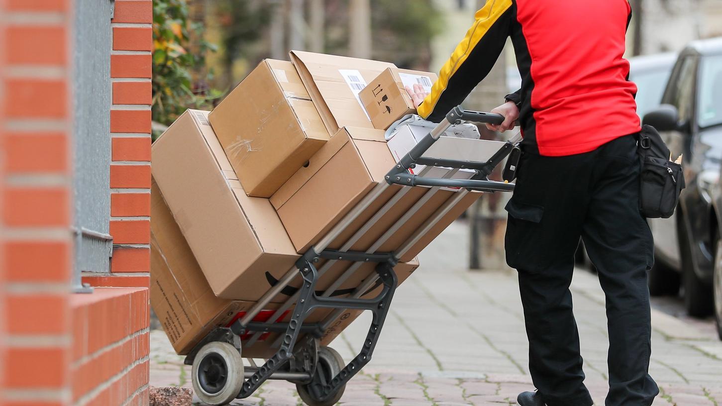 Ein Paketzusteller geht mit einer Sackkarre voller Pakete zu einem Haus.