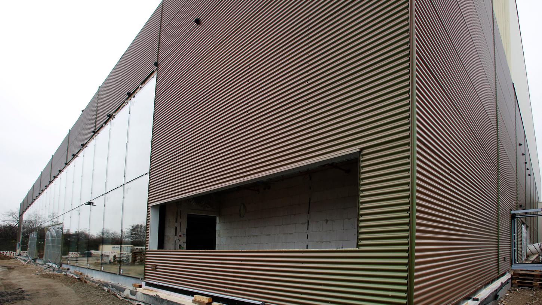 Mit Glasfront und Lamellenfassade in verschiedenen Farben: Das ist die neue Halle der Stadt am Tillypark.