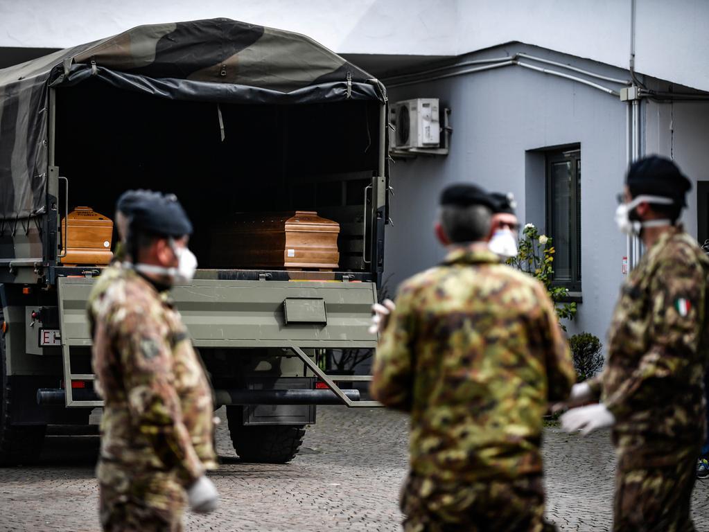 27.03.2020, Italien, Cinisello Balsamo: Italienische Armeesoldaten mit Mundschutz warten darauf, dass die Särge aus der Gegend von Bergamo aus dem Militärfahrzeug in ein Gebäude des Friedhofs von Cinisello Balsamo getragen werden. Foto: Claudio Furlan/LaPresse/AP/dpa +++ dpa-Bildfunk +++