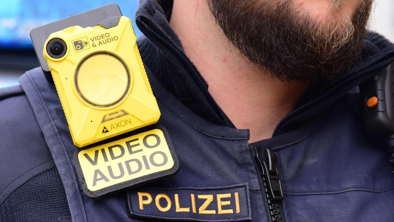 Die Body-Cam wird in eine Schlaufe auf der Polizeiweste eingehängt. Über den Schieberegler (rechts oben) wird sie entriegelt und über den Knopf (mittig) aktiviert.