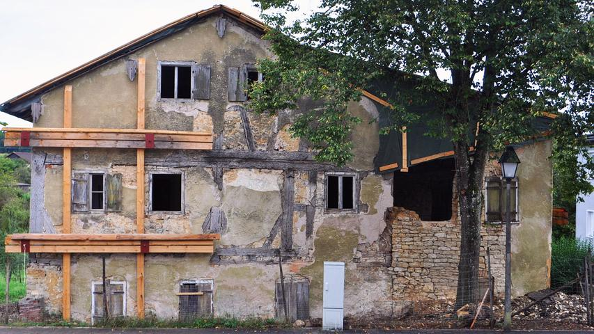 Von der Dorfstraße aus erkennt man gut das einstige Gasthaus (links) und das im 19. Jahrhundert angebaute, inzwischen stark verfallene Korbhaus (rechts).