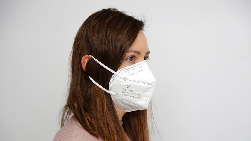Alle, die ihre Haare gerne offen tragen, sollten darauf achten, sie über die FFP2-Maske sowie die Spannbänderzu legen - und nicht darunter. Ansonsten liegt die Maskean den Wangen nicht richtig an.