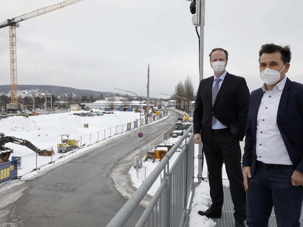 Peter Hackenschmied (links), Leiter der Produktsparte Power und Vacuum und Thorsten Reichert, Projektmanager des neuen HEP Centers, blicken auf die Baustelle.
