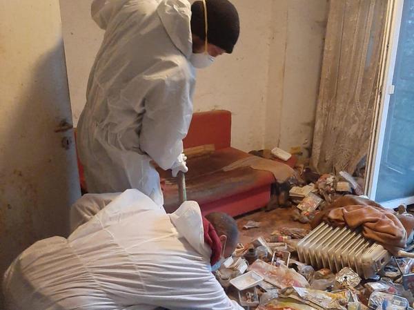 Arbeiter in Schutzanzügen beim Räumen einer Messie-Wohnung.