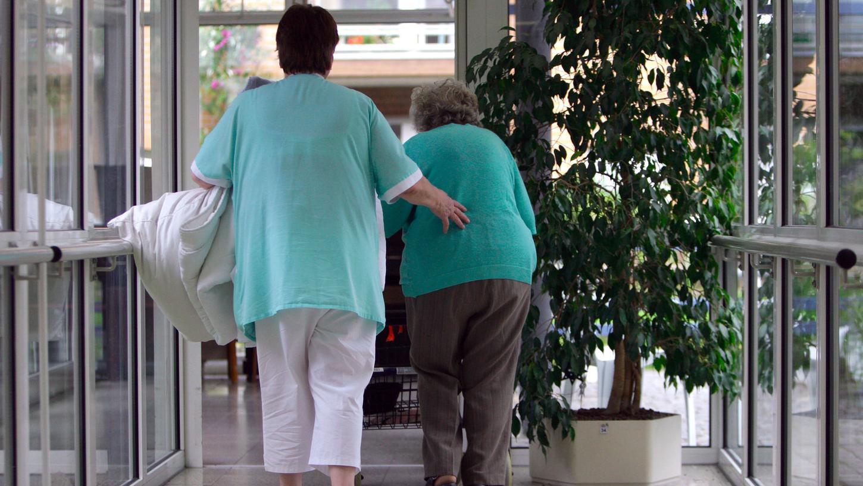 Eine Altenpflegerin gehtmit einer Seniorin durch einen Flur