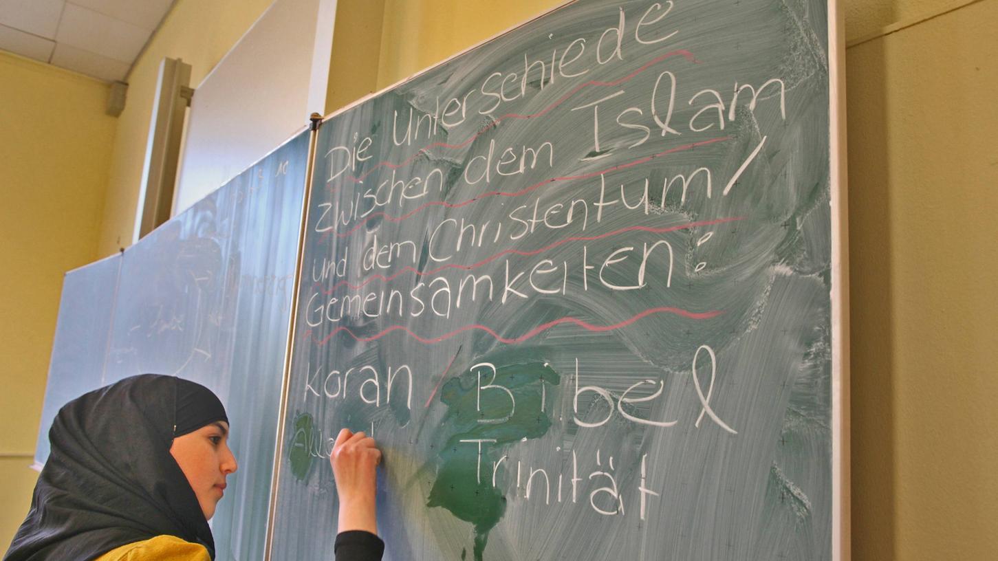 Eine muslimische Schülerin schreibt im Islamunterricht Begriffe an die Tafel. In Bayern wird das Fach bisher an über 360Schulen unterrichtet.