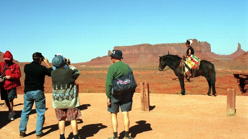 Foto: imago images/BRIGANI-ART - ..1/ Reise: Indianermädchen auf Pferd im Monument Valley in Arizona, bizarre Steinformation, roter Sandstein, Wüste, Trockengebiet, Attraktion, Sehenswürdigkeit, Urlaub, Tourismus, bekannte Touristengegend, Touristenattraktion, Reiseziel, Urlaubsziel, Erholung, Landschaft, Landschaftsbild, Landschaftspanorama, Panorama, Amerika, Mädchen, Indianer, Indianerpony, Pony, Touristen fotografieren, Urlauber, Indianerkind, Arizona United States Of America *** 1 Trip Indian girl on horseback in Monument Valley in Arizona, bizarre rock formation, red sandstone, desert, arid area, attraction, sight, attraction, vacation, tourism, famous tourist area, tourist attraction, destination, holiday destination, recreation, landscape, scenery, landscape pa Copyright: xBriganiArt/ArtistxAtxWork/Heinrix 0003352700033527