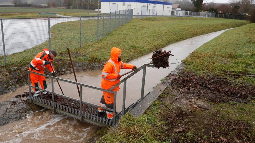 Viel Wasser im Jägersburger Graben: Mitarbeiter der Stadt Forchheim versuchen, ein Wehr vor angeschwemmtem Material freizuhalten, um Überschwemmungen zu vermeiden.