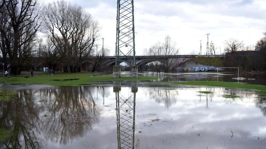 Die Rednitz ist über die Ufer getreten und überschwemmt Wiesen und Wege rund um die Siebenbogenbrücke.
