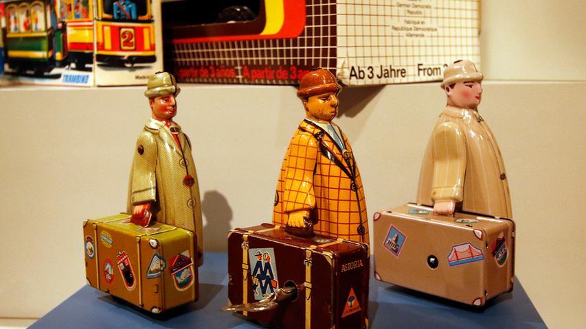 Reisende aus drei Blechspielzeugfirmen: Der Mann mit dem Koffer links stammt aus den 1950ern von der Zirndorfer Firma Fritz Voll. Die VEB Mechanische Spielwaren Brandenburg stellten zu DDR-Zeiten den mittleren Mann her. Und der rechte Kofferträger kam 2013 aus chinesischen Werkstätten.