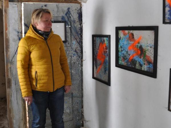 """Bürgermeisterin Regina Bruckmann steht in der """"hidden gallery"""" vor den Bilderrahmen, die von den Unbekannten ebenfalls besprüht worden sind."""