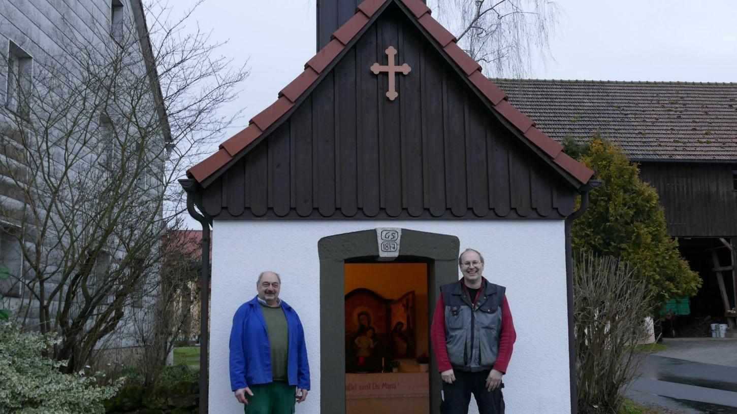 Der Vorbeter Hans Thiem (links) und Ortssprecher Peter Thiem aus Pfaffenberg (rechts) sind stolz auf ihre über 200 Jahre alte Kapelle in der Mitte des kleinen Ortes.