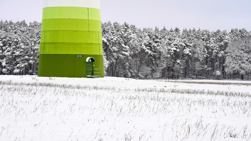 Zartes Grün im frischen Schnee. Der Zugang eines Windradturms hebt sich leuchtend vom Weiß ab.