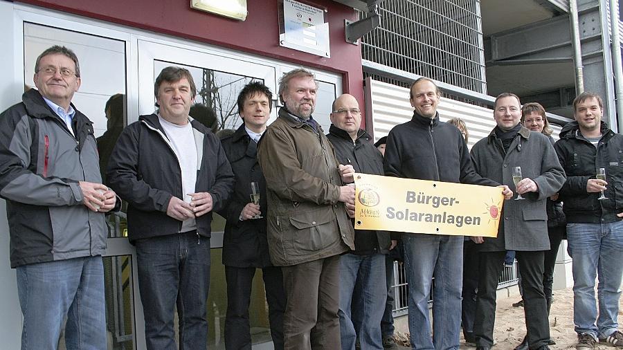 Dr. Gerhard Brunner und Martin Sauer (vorne) mit einigen Teilhabern der Bürgersolaranlage vor dem Bahnhofs-Parkhaus. Über ihnen zeigt ein Display an, wie viel Strom die PV-Anlage produziert. Links Ernst Hofer von den Stadtwerken, die den Strom abnehmen, Dritter von links Thorsten Gmeiner vom Bahnhofsmanagement Nürnberg.