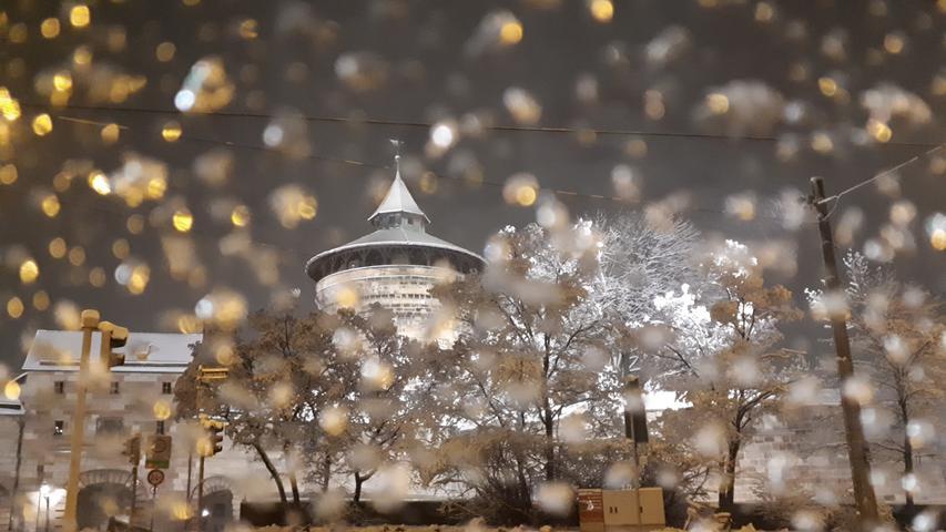 Durchs Fenster fotografiert sieht es aus, als wäre das Nürnberger Neutor in einer Schneekugel mit Glitzerschnee eingeschlossen.