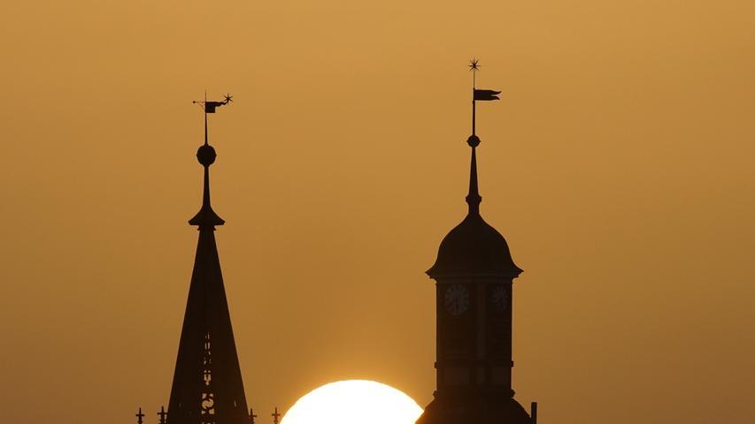 Wie ein Scherenschnitt, aber mit einem durch Saharastaub leicht gedämpften Sonnenball: Heilsbronn mit Münster und Katharinenturm.