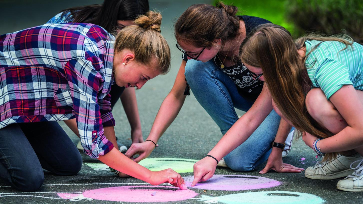 Aus einer Zeit, als es noch Freizeitprogramm für Jugendliche gab: Mädchen malen mit Straßenkreide auf der Burg Feuerstein bei Ebermannstadt.