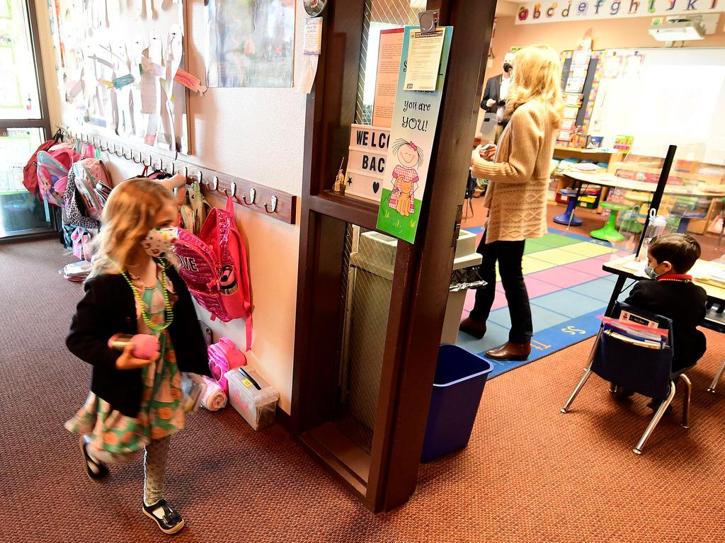 February 22, 2021, Rancho Cucamonga, California, USA: St. Peter and St. Paul Catholic School kindergarten student Raegan Scott, 6, walks into class on her first day of in room instruction in Rancho Cucamonga Monday morning Feb. 22, 2021 as her teacher Joann Losciale looks on. It was the first day students have attended in room classes at the school since last March due to the COVID-19 pandemic. Rancho Cucamonga USA - ZUMAo44_ 20210222_zan_o44_020 Copyright: xWillxLesterx