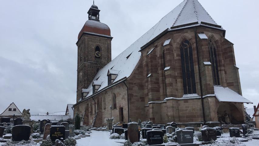 Winter-Stille: Schnee bedeckt die St.Laurentiuskirche in Roßtal und die Gräber des Friedhofs.