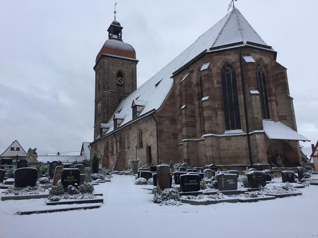 Winter-Stille: Schnee bedeckt die St.Laurentiuskirche Roßtal und die Gräber des Friedhofs.