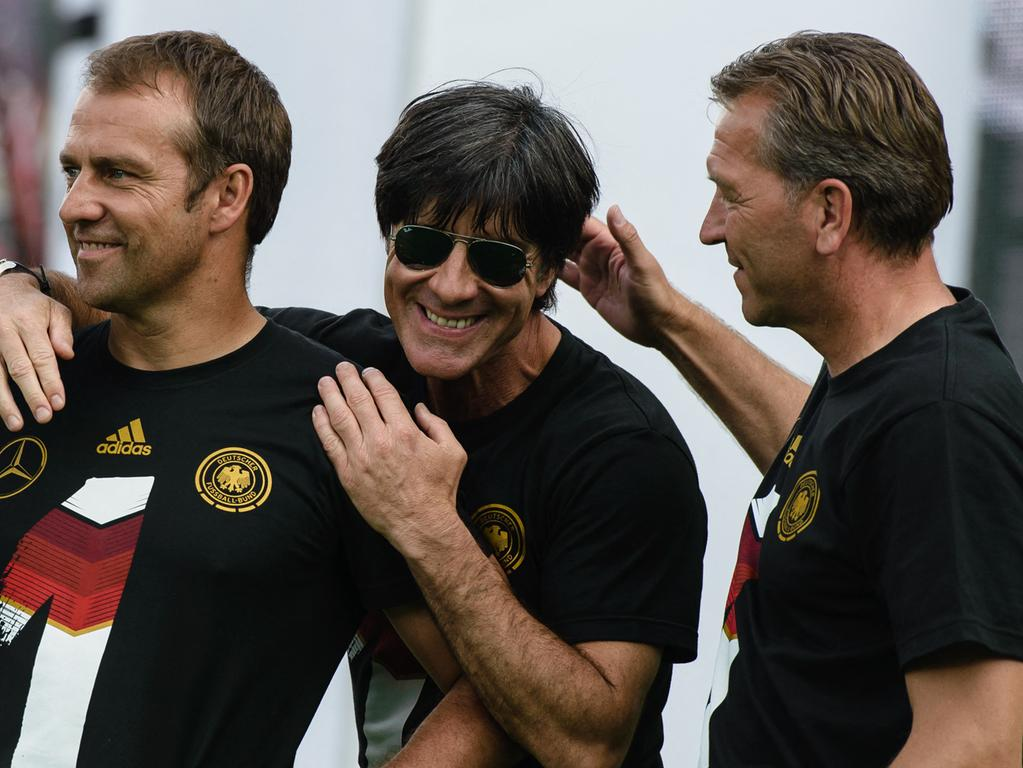 (FILES) This file photo taken on July 15, 2014 shows (R-L) Germany's goalkeepers' coach Andreas Koepke, Germany's coach Joachim Loew and Germany's assistant coach Hans-Dieter Flick celebrating during a victory parade of Germany's national football team at Berlin's landmark Brandenburg Gate to celebrate their FIFA World Cup title. - Germany's World Cup-winning head coach Joachim Loew will step down after the European championships this July, the German FA confirmed on March 9, 2021. (Photo by CLEMENS BILAN / AFP)