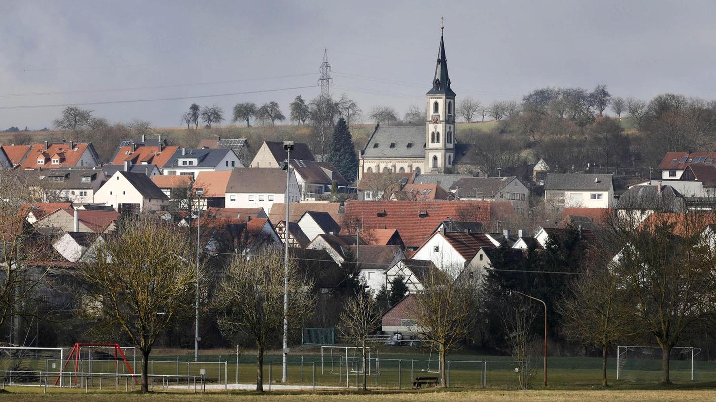 """Vorne der Sportplatz, hinten die Kirche: Hallerndorf liegt idyllisch im Aischtal. Der Bürgermeister lobt den Zusammenhalt im Ort, die Kultur- und die Naturlandschaft. """"Da bin ich daheim, da fühle ich mich wohl"""", sagt Gerhard Bauer über sein Heimatdorf."""