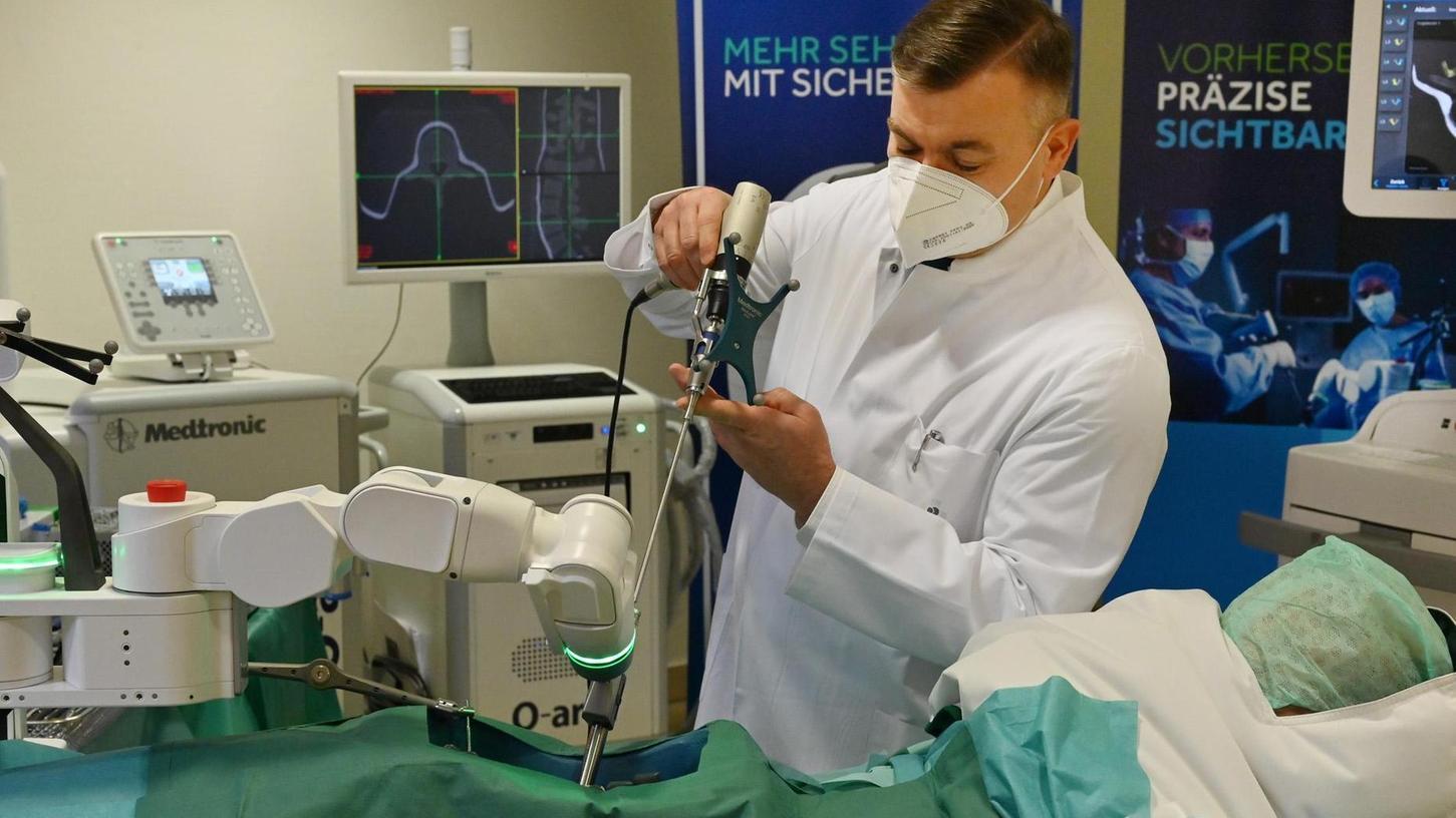 Modernste Technik im Erlanger Waldkrankenhaus: Chefarzt Klaus Schnake präsentiert den OP-Roboter, der in der Wirbelsäulenchirurgie zum Einsatz kommt.