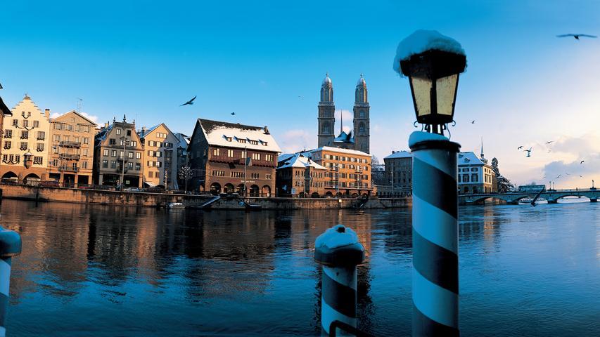 Wer Glück hat, kann bei gutem Wetter in Zürich einen solchen Anblick genießen. Hinter dem Limmat ragen die beiden Türme des Großmünsters in den Himmel über Zürich. Swiss International Airlines hebt seit August wieder in die Schweiz ab.