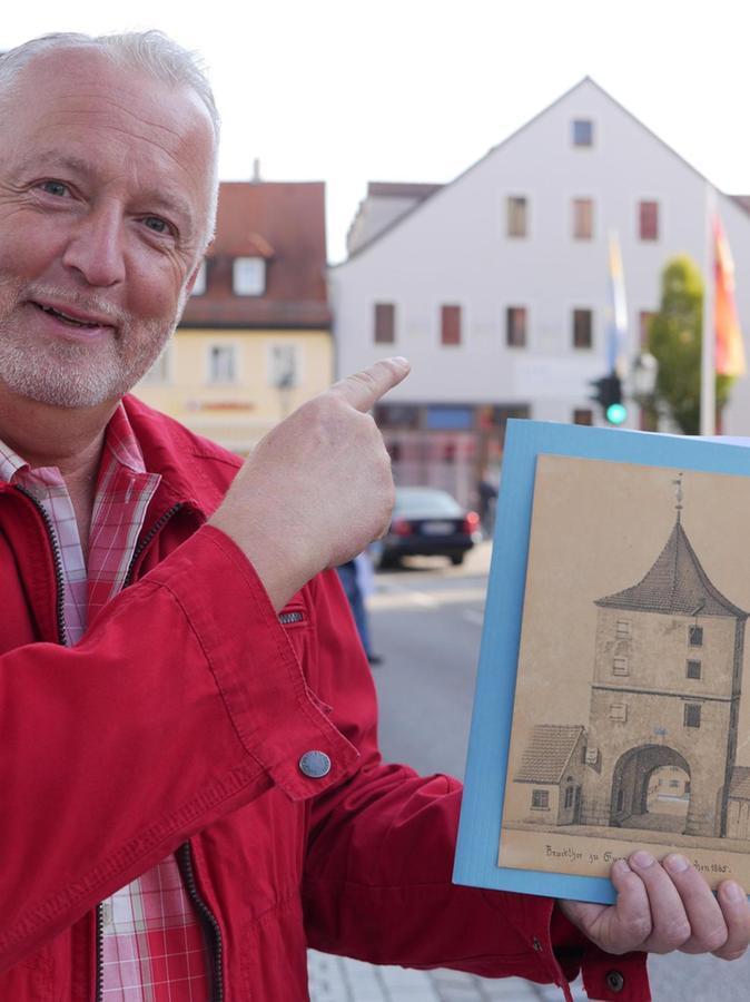 """Genau am früheren Standort des Brucktors hält Werner Mühlhäußer eine Originalzeichnung von 1865 aus dem Fundus des Stadtarchivs ins Bild. Im Hintergrund das heutige Hotel """"Blauer Wolf"""", die frühere Wohnung eines gewissen Herrn Hunger."""