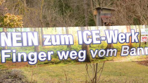 Mit Ablehnung im Blick präsentiert Sophie Wurm vom Bund Naturschutz in ihrem Garten das neue Banner, das schon bald an mehreren Orten in der Marktgemeinde zu sehen sein wird.